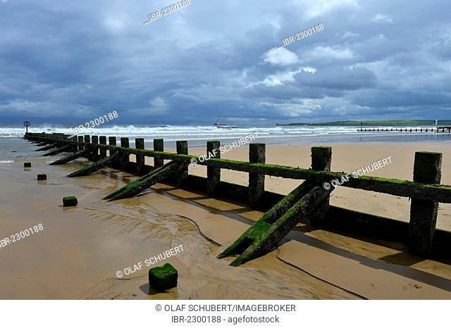 Thick, low hanging cloud cover above moss and algae covered groynes, breakwaters, at the beach, Aberdeen Scotland, United Kingdom, Europe