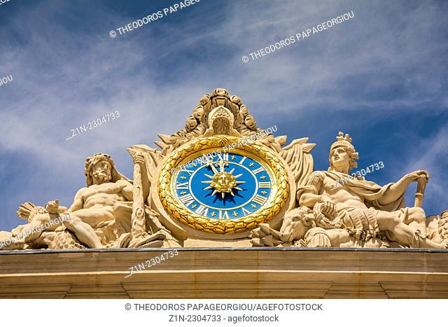 The clock and sculpture of Hercules above the main entrance to the Palace of Versailles, France