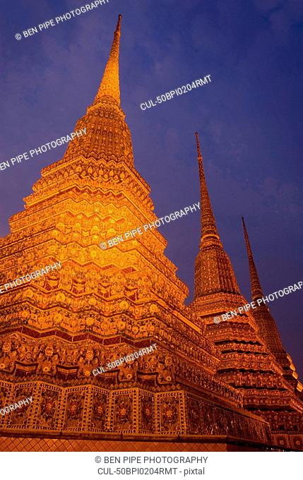Ornate carved spires lit up at night