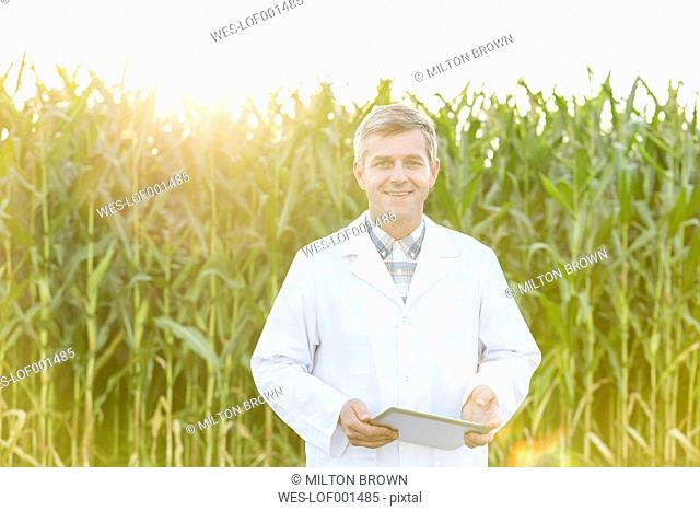 Smiling scientist with digital tablet at corn field