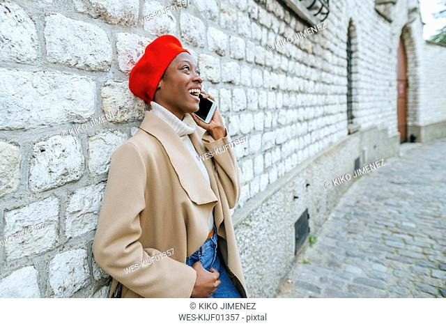 Young woman in Paris leaning against wall and talking on the phone
