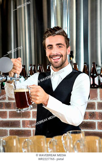 Barman pouring beer