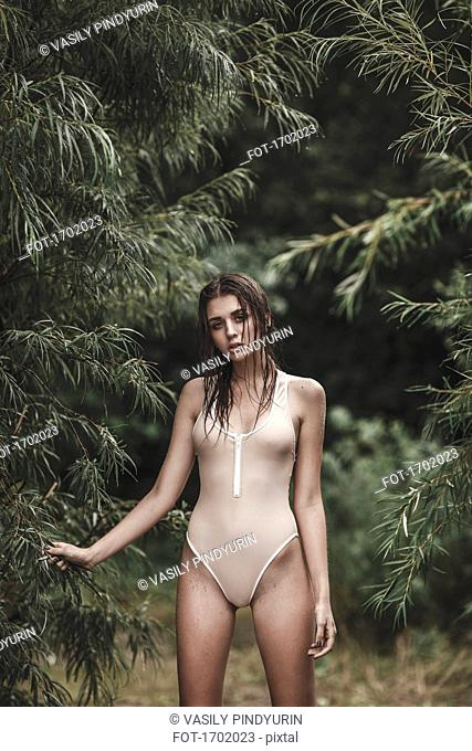 Portrait of young woman wearing one piece swimsuit standing amidst trees at forest