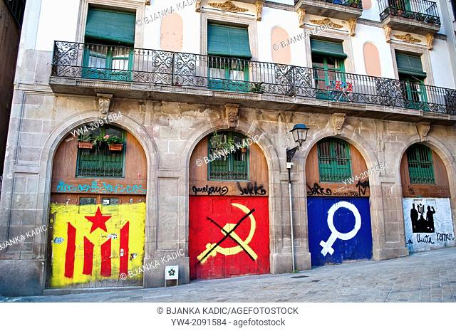 Catalan flag, communist and feminist symbols painted on house in Placa del Fossar de les Moreres, Ribera district, Barcelona, Spain