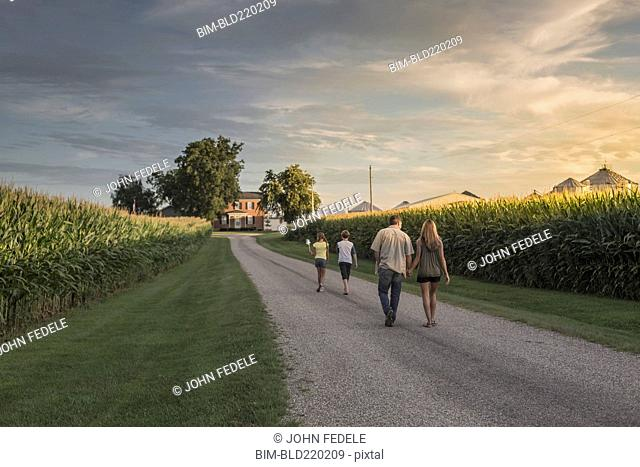 Caucasian family walking on dirt path by corn field