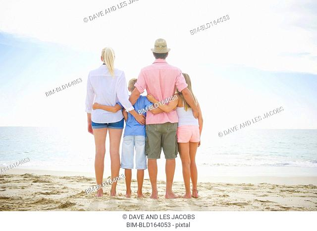 Caucasian family hugging on beach