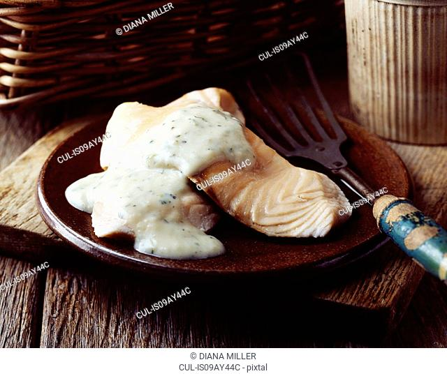 Grilled salmon with white sauce on vintage plate