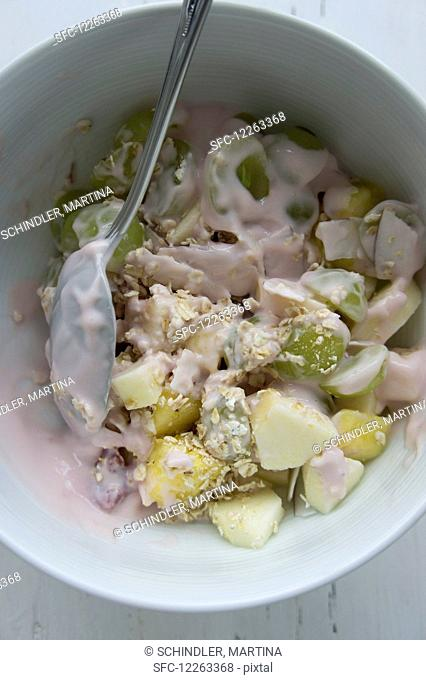 Muesli with oatmeal, grapes, mango, apples, dessicated coconut and yogurt made from coconut milk