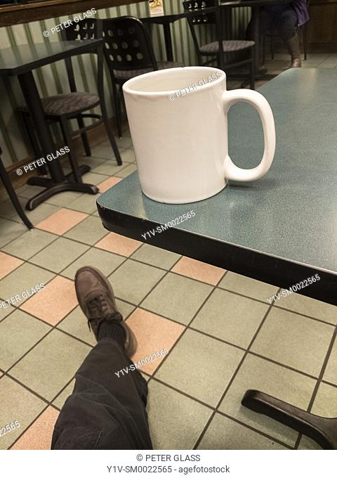 Man's leg and foot near a table with a mug on it, in an empty cafe