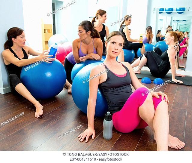 Aerobics pilates women group having a rest at gym talking and having fun