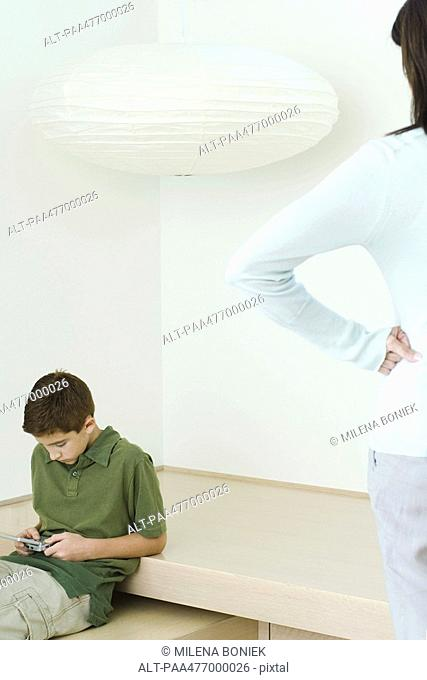 Boy playing video game, mother watching, hands on hips
