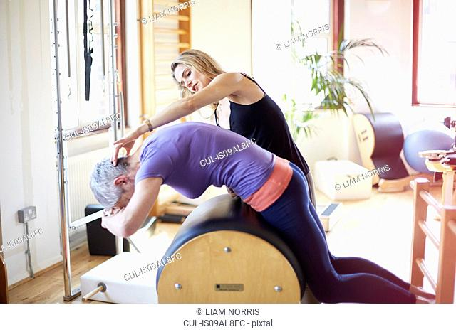 Mature female student leaning forward onto pilates barrel in pilates gym