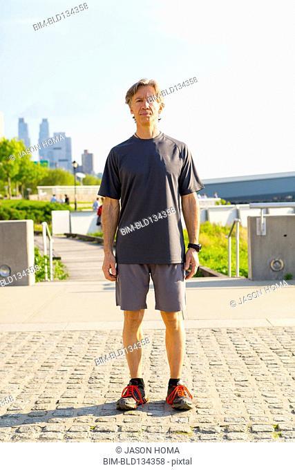 Caucasian runner standing in urban park
