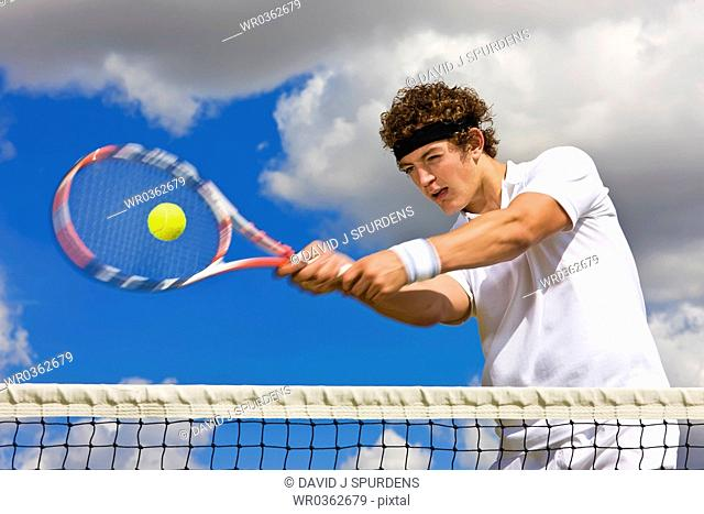 Tennis player concentrating on returning ball at net