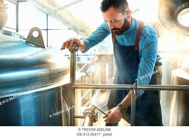 Male coffee roaster checking tank gauge