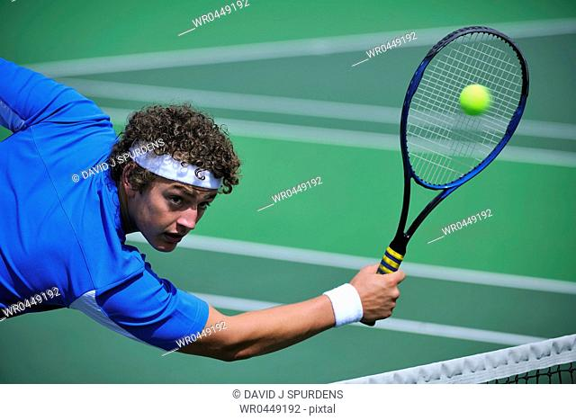 Male tennis player dives to return ball