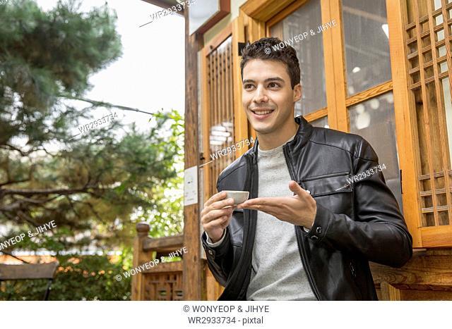 Smiling man drinking traditional Korean tea