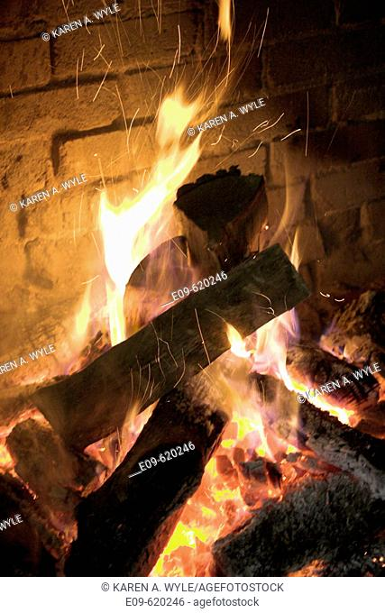 fire in stone or brick fireplace, glowing pink-orange and yellow coals, yellow and white flames reaching up, sparks rising