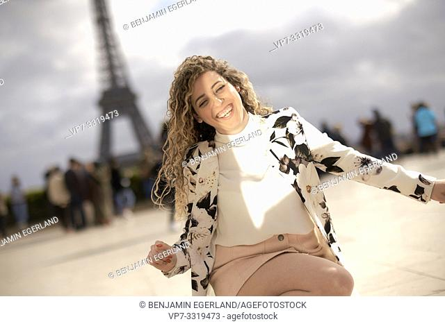 woman crouching and dancing outdoors in public in city next to tourist sight Eiffel Tower, at Espl. du Trocadéro, in Paris, France