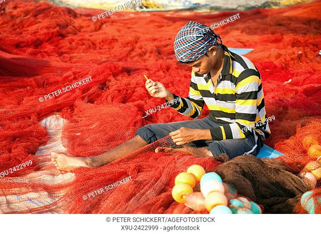 young fisherman repairing his red net on the beach in Benaulim, Goa, India, Asia