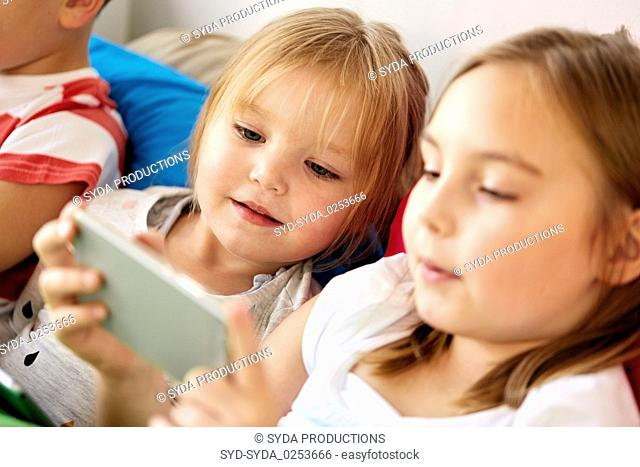 little kids with smartphone in bed at home