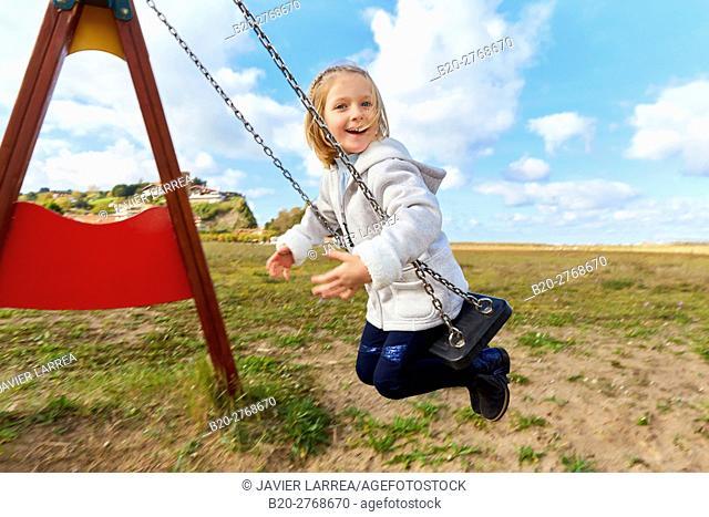 Girl playing on a swing, Zumaia, Gipuzkoa, Basque Country, Spain