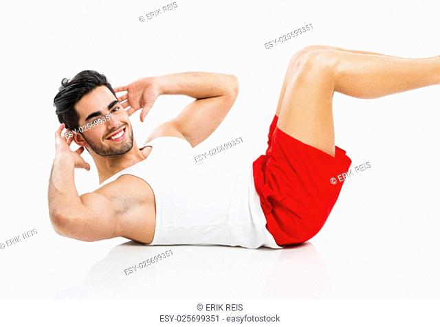 Athletic young man doing ABS, isolated over a gray background