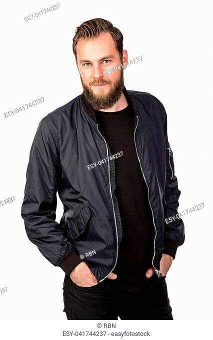 Handsome bearded man standing against a white background wearing a black tshirt and blue jacket in jeans. Looking at camera