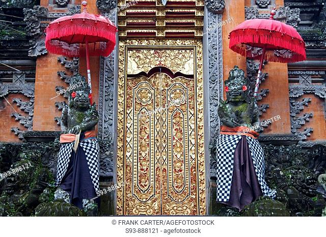 A gilded door of a Balinese temple with two stone figures under red traditional umbrellas on each side in Ubud, Bali