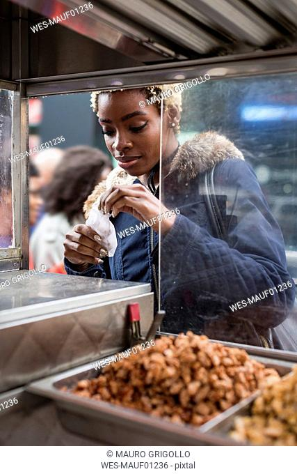 Portrait of young woman buying food on stall