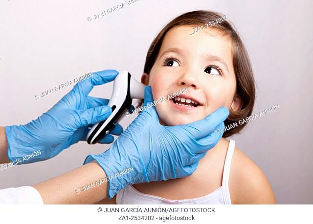 Doctor measuring temperature happy little girl with ear talking electronic thermometer. Isolated over white background