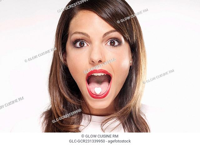 Woman with mint candy on her tongue