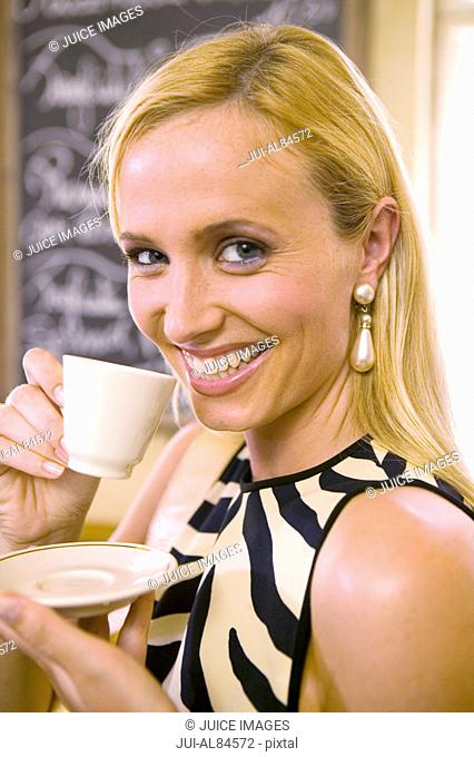 Close up of woman drinking espresso in restaurant
