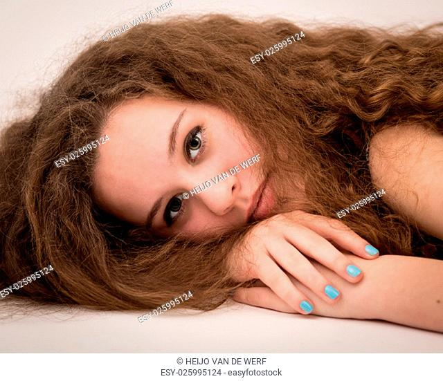 Studio portrait of a beautiful teenage ginger girl with long thick curly hair laying on the floor and nails painted blue with nail polish