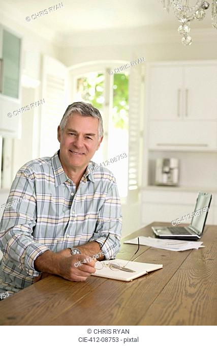 Portrait of senior man at kitchen table