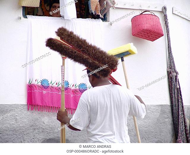 a person selling domestic objects brooms