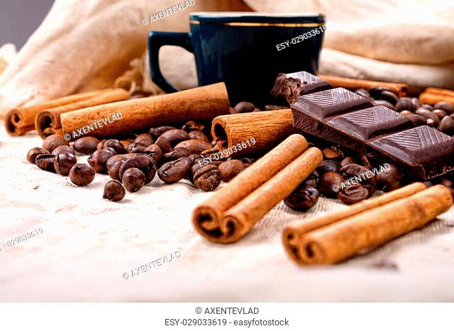 Cup of hot coffee with cinnamon sticks, bitten bar of chocolate on vintage texture background, selective focus