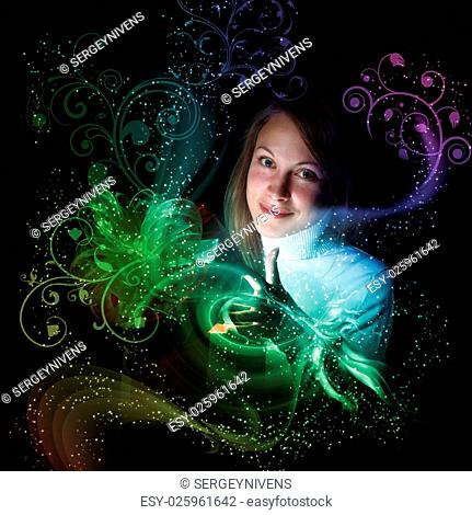 Young woman opening a gift box with shining and glittering lights around her