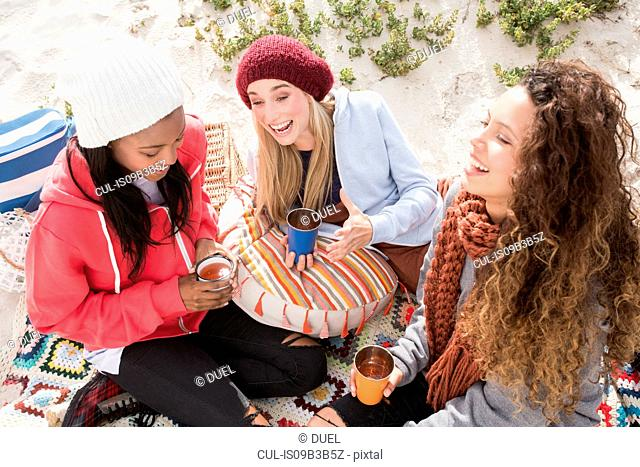 Three young women laughing on beach picnic, Western Cape, South Africa