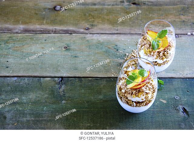 Detox Greek yogurt, granola, peach layered parfait in glasses with mint leaves
