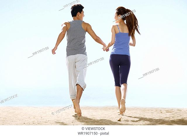 The romantic lovers walking on the beach