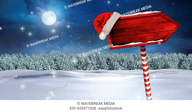 Wooden signpost in Christmas Winter landscape and Santa hat