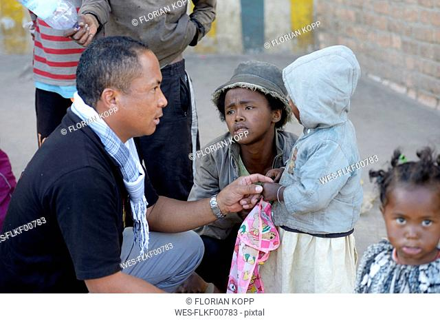 Madagascar, Fianarantsoa, Social worker talking to a homeless young mother and her child