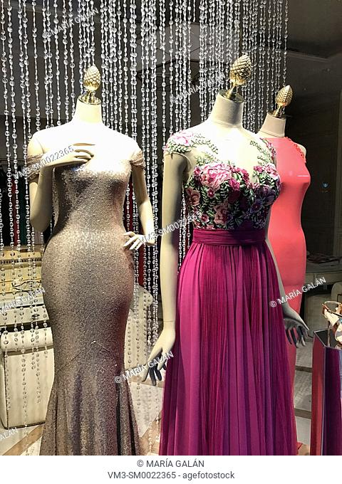 Three mannequins wearing evening dresses in a shop window. Madrid, Spain