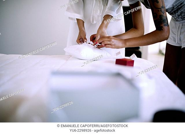 Woman hands tie wedding rings on white cushion
