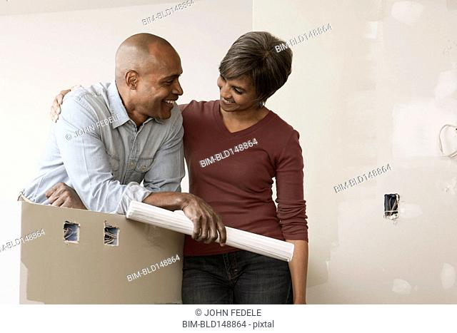 Couple standing in unfinished room with blueprints
