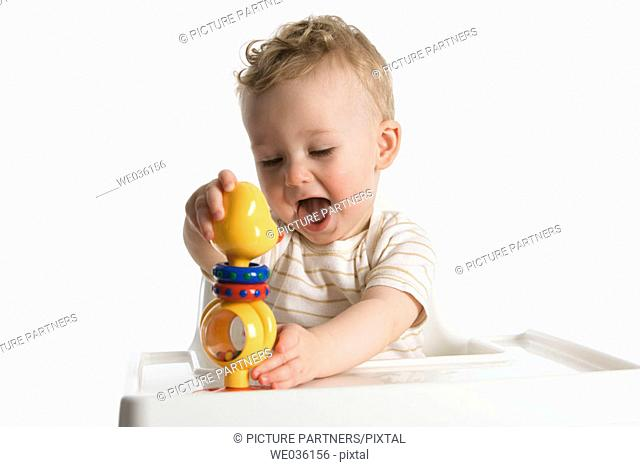 Little boy playing with a plastic rattle doll