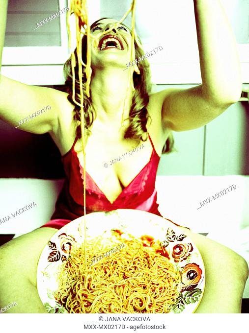 Young woman sitting with spaghetti on her head