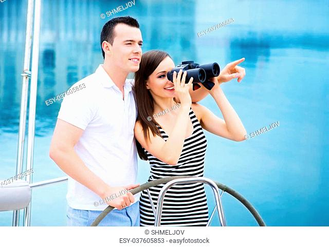 A young and happy Caucasian couple relaxing on a boat and looking through binoculars