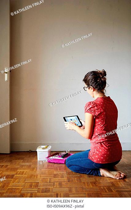Woman kneeling beside decorating equipment, looking at digital tablet, rear view